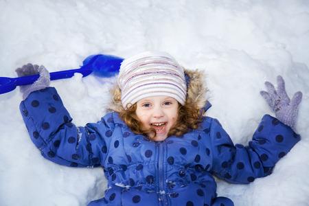 Ni�a que juega en la nieve con una pala.