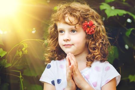 niño orando: La niña cruzó las manos en oración.