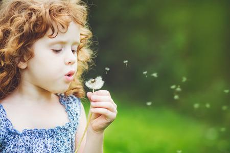 persona respirando: niña rizada sopla el diente de león
