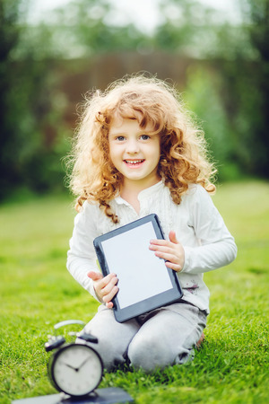 Happy surprised child with laptop sitting on the grass. Stock Photo