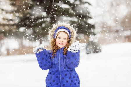 Surprised funny girl raised her hands in the air, catching snowflakes in winter park.