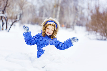 Little happy girl hand up and smiling, sitting in the snow park. Stock Photo