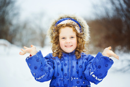 christma: Happy little girl sends a kiss, playing in the snow park.
