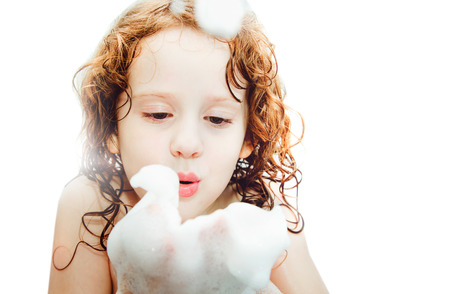 soap sud: Happy little girl blowing foam with her hand isolated on white background.