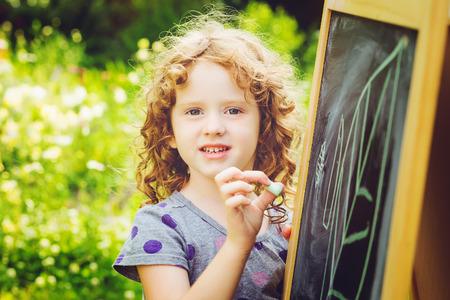 Girl writes in chalk on a blackboard. Education concept. Toning photo.