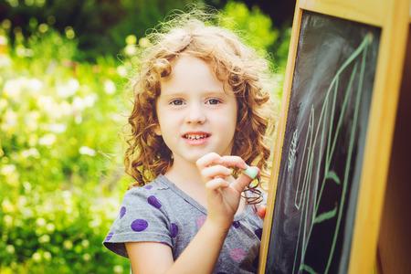 La muchacha escribe con tiza en una pizarra. Concepto de educaci�n. Tonificaci�n foto.