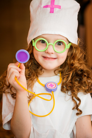 auscultate: Curly girl playing doctor with a stethoscope. Stock Photo