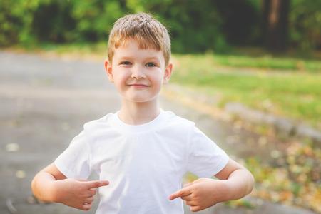 Heureux petit garçon pointant ses doigts sur un t-shirt blanc, un endroit pour votre publicité. concept de la petite enfance. Banque d'images