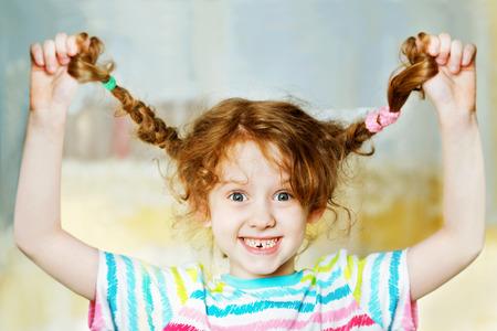 웃음 소녀 손으로 그녀의 땋은 끌어와 그녀의있는 teeths을 보여줍니다. 어린 시절 개념.