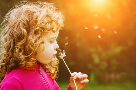 Fille soufflant pissenlit dans les rayons du soleil. Le gainage pour filtre Instagram. Banque d'images