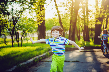 Happiness child running on the park on sunset rays. Background toning  photo