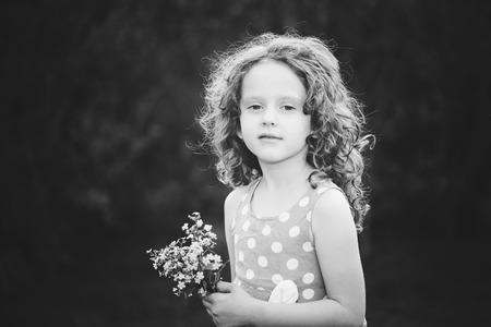 Ni�a hermosa con una flor en la mano. Foto blanco y negro.