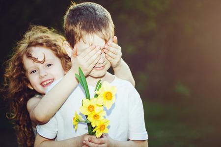 dar un regalo: Bella joven que cubre los ojos de su novio y muchacho con las flores del ramo en la mano.