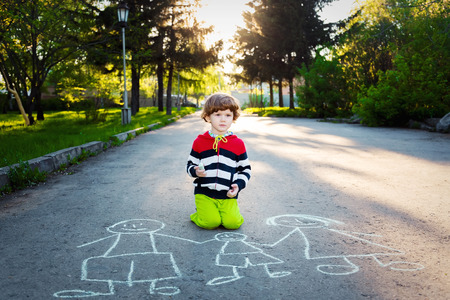 Child draws on asphalt. Stock Photo
