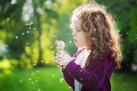 Pretty girl blowing dandelion.