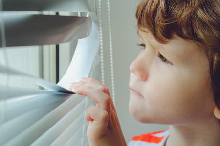 Petit enfant regardant par la fenêtre à travers les stores. Banque d'images