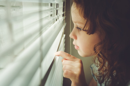 Little child looking out the window through the blinds.