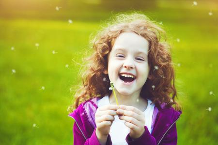Child with white dandelion in your hand.   Foto de archivo