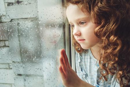 mirada triste: Niño triste mirando por la ventana. Tonificación foto. Foto de archivo