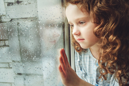window: Sad child looking out the window. Toning photo. Stock Photo