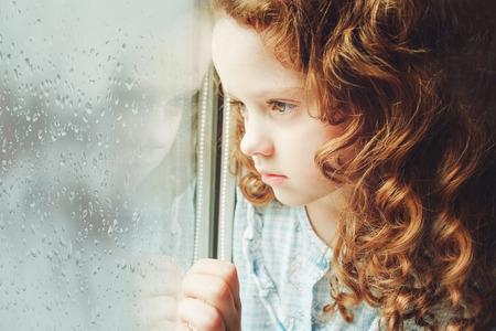 kinderschoenen: Droevig kind kijkt uit het raam. Toning foto. Stockfoto