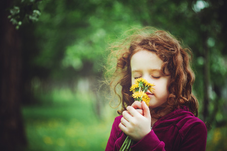 Little girl closed her eyes and breathes yellow dandelions in the field. Background toning to instagram filter.
