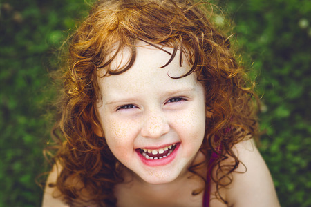Laughing redheaded girl with freckles.