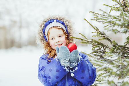 decorates: Little girl decorates the Christmas tree.