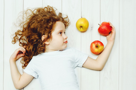 Happy child with red apples on light wooden floor. Top view.