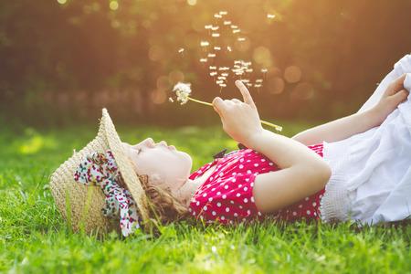 L'enfant pose sur l'herbe et le pissenlit soufflant dans les rayons du soleil. Banque d'images