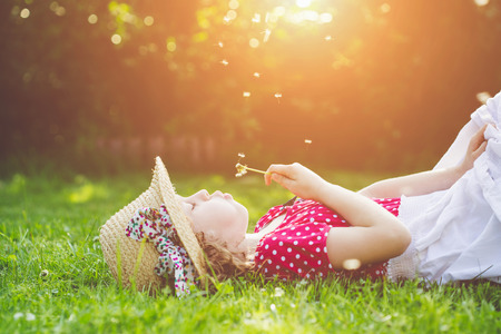 The child lays on a grass and blowing dandelion in the rays of the sun.  Stock Photo