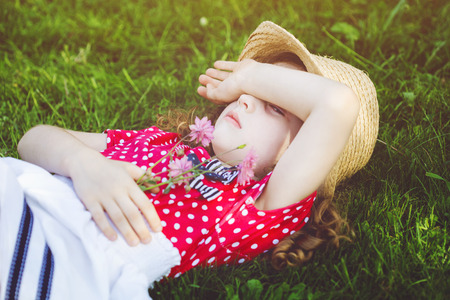 dolorous: Offended little girl lies in the green grass and closed hands her face.