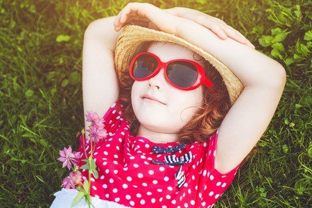 Happy girl with glasses lying on the grass in a summer park. Happy childhood concept.