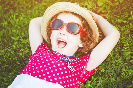 Happy laughing girl with glasses lying on the grass in a summer park. Happy childhood concept.  Imagens