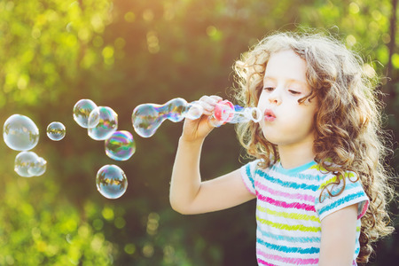 Cute girl blowing soap bubbles, closeup portrait. Stock fotó - 42506151