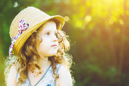 Little girl in a straw hat  at sunset. Freedom concept. Stock Photo