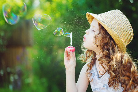 심장 모양의 비누 거품을 불고 사랑스러운 작은 소녀. 행복 어린 시절 개념.