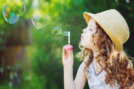 Bella bambina che soffia bolle di sapone a forma di cuore. Concetto di infanzia felice.