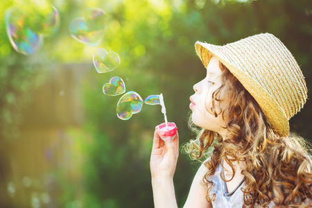 Cute girl blowing soap bubbles in a heart shape. Happy childhood concept.