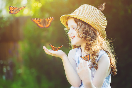 Laughing little girl with a butterfly on his hand. Happy childhood concept. Standard-Bild