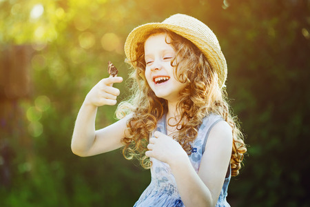 Laughing curly girl with a butterfly on his hand. Happy childhood concept.