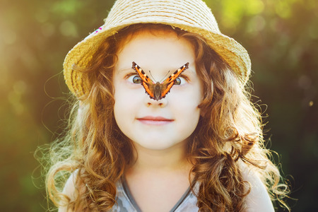 Surprised girl avec un papillon sur le nez, se concentrer sur le visage d'une jeune fille.