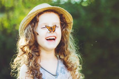 Rire fille bouclés avec un papillon sur sa main. Concept enfance heureuse.