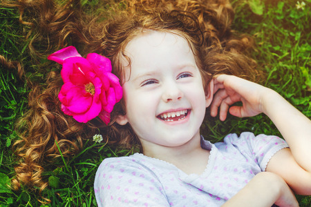 Happy laughing girl with rose in her hair in green grass at summer park. Happy childhood concept.