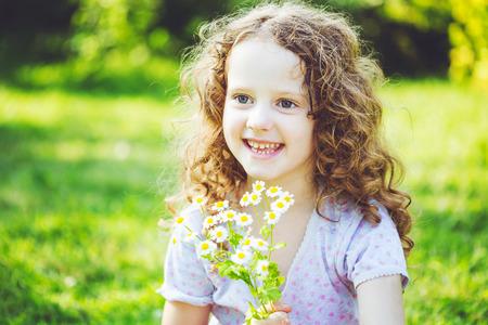 Sonriente ni�a con un ramo de margaritas blancas. Madres concepto d�a. Antecedentes entonado en el filtro de Instagram.