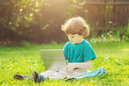Ni�o feliz jugando port�til sentado en la hierba verde en el parque de verano.