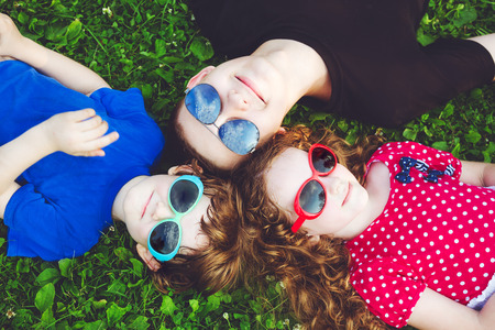 happy family concept: Happy children in glasses lying on the grass. Happy family concept. Stock Photo