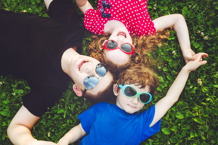 brother: Happy children in glasses lying on the grass. Happy family concept. Stock Photo