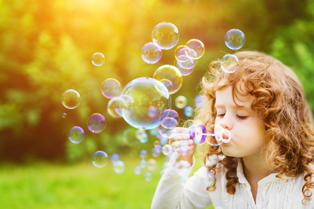 spring green: A little girl blowing soap bubbles in summer park. Background toninf for instagram filter. Stock Photo