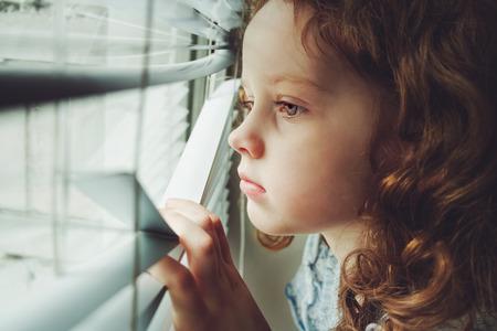 occhi tristi: Bambina triste guardando fuori dalla finestra attraverso le persiane. Sfondo tonificante a Instagram filtro.
